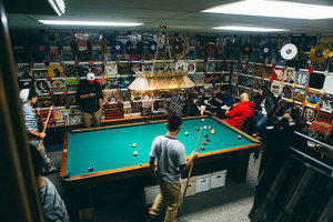 Image of people playing pool in a garage, surrounded by walls of record sleeves