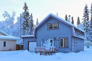 Image of a snowy home with a garage and table outside