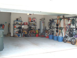 Image of a tidy garage with tools and items on racks against the wall leaving space for cars