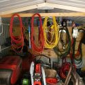 Image or tidy garage with cables, lawnmowers and other items tidily stored