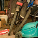 Image of bikes and a lawnmower in an untidy garage