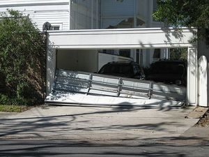 Image of a damaged garage door exposing 2 cars